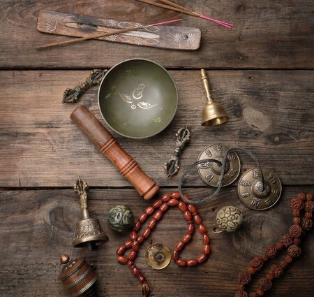 Copper singing bowl, prayer beads, prayer drum and other Tibetan religious objects for meditation and alternative medicine on a brown wooden background 写真素材