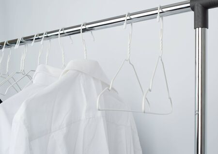 white mens crumpled shirts hanging on a metal hanger, white background