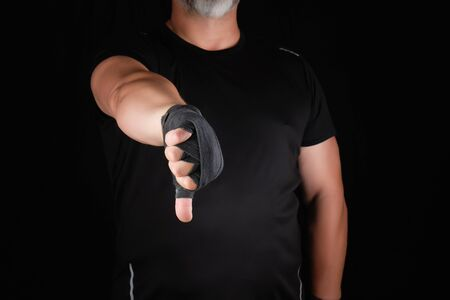 adult athlete in black uniform and hands rewound with textile bandage shows gesture dislike, low key