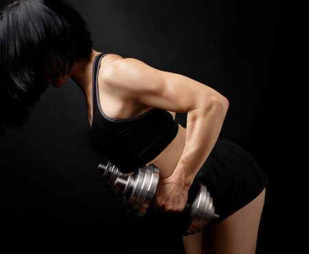 adult girl with black hair is dressed in a sports bra and short shorts is doing physical exercises on the arm muscles with a steel dial dumbbell, low key Stok Fotoğraf
