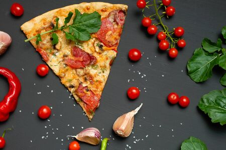 triangular slice of baked pizza with mushrooms, smoked sausages, tomatoes and cheese, next to fresh green leaves of arugula, black background, flat lay
