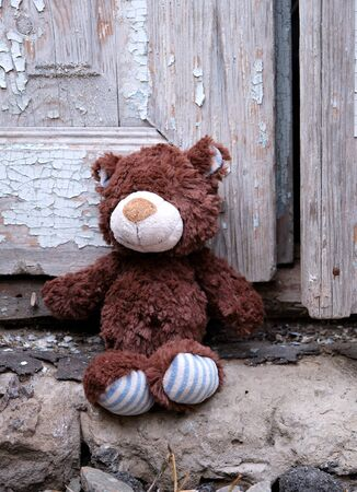 little teddy bear sits on the doorstep near an old door with cracked paint, close up