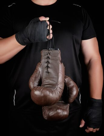 athlete in black clothes holds very old vintage leather brown boxing gloves, low key Фото со стока
