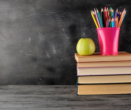 stack of books and  multi-colored wooden pencils, background of an empty black chalk board, back to school concept Фото со стока