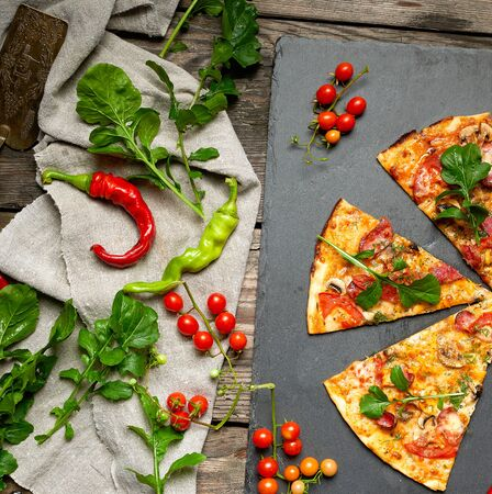 baked round pizza with smoked sausages, mushrooms, tomatoes, cheese and arugula leaves, food is cut in portions, wooden table