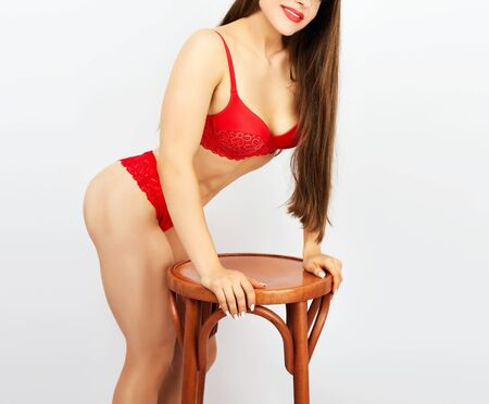 beautiful girl with a sports figure dressed in red lace underwear stands in a sideways position and rests on a brown wooden chair, white background