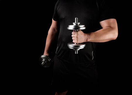 man in black clothes holds steel dumbbells in his hands, his muscles are tense, low key, sports background