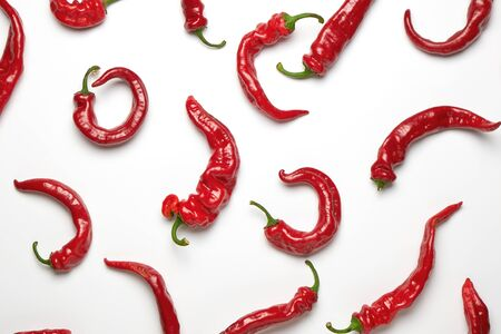 whole ripe red hot pepper scattered on a white background, fragrant spice for cooking, full frame