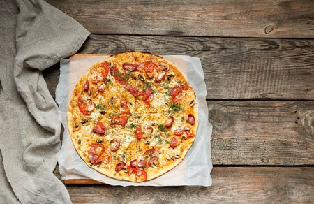 baked round pizza with smoked sausages, mushrooms, tomatoes, cheese and arugula leaves, food is cut in portions, wooden table, copy space