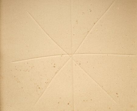 fragment of a brown paper sheet of a box with greasy stains, close up