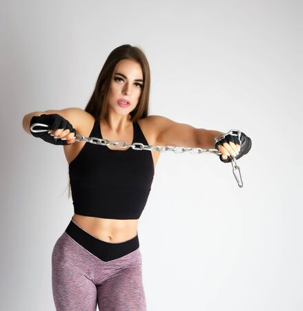 beautiful young girl with long blond hair, athletic appearance holds a metal chain, dressed in leggings and a black top, white background