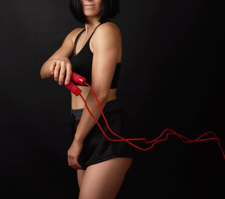 young woman with a sports figure in black uniform holds a red rope for jumping, low key