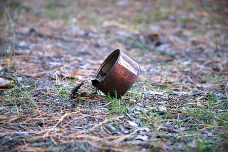 rusty open tin can lying in the middle of the forest, environmental pollution concept