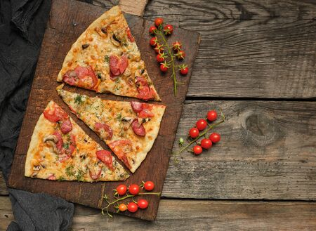 baked pizza with smoked sausages, mushrooms, tomatoes, cheese and dill, sliced food on a brown wooden board, close up