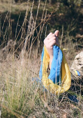 male hand of a Ukrainian army soldier raised up among the grass and holds the state yellow-blue flag, concept of the memory of the dead soldiers