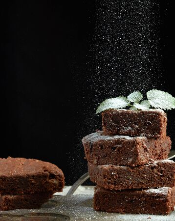 stack of square baked brownie chocolate cake slices sprinkled with white sugar, small particles fly down, low key Фото со стока