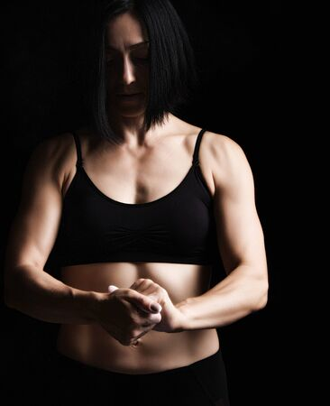 beautiful young girl with a sports figure dressed in a black top claps in her hands with white magnesia, preparing before exercise, low key