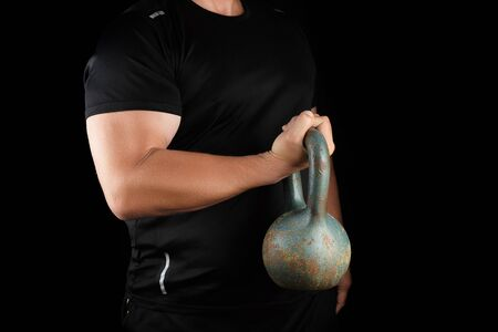adult strong athlete in black clothes holding an iron kettlebell on his outstretched arms, black background Фото со стока