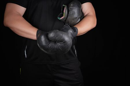 adult muscular man in black clothes puts on leather black boxing gloves on his hands before a competition, his hands are wrapped in a black sports bandage