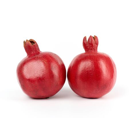 two ripe red pomegranates in a peel on a white background, close up  Фото со стока