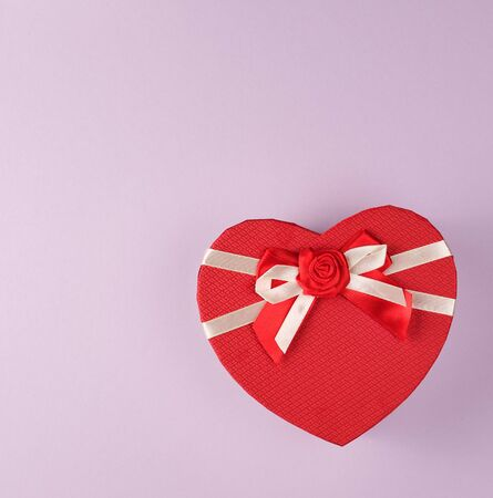 closed red gift box in the form of a heart with a bow on a purple background, copy space