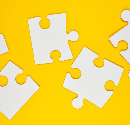 blank white big puzzles on yellow background, flat lay, copy space