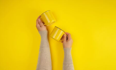 two yellow ceramic cups are supported by a female hand on a yellow background, copy space