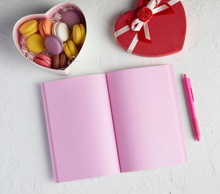 open notebook with blank pink pages, red pencil and a box of sweets, top view