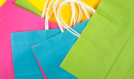 many multi-colored paper shopping bags with white handles on a yellow background, flat lay