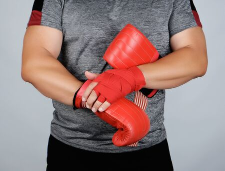 athlete in blue clothes, hands are rewound with red textile bandage, he is wearing leather sports boxing gloves, gray background Фото со стока