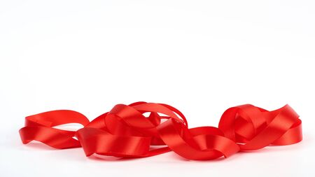 curled red satin ribbon on white background, festive backdrop, close up