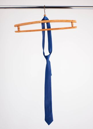 blue tie hanging on a wooden hanger, white background