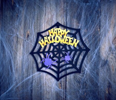 white spider web in the corner of the composition, gray wooden background from old boards, backdrop for Halloween holiday