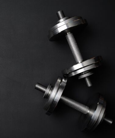 pair of shiny steel typesetting dumbbells for bodybuilding on a black background, top view