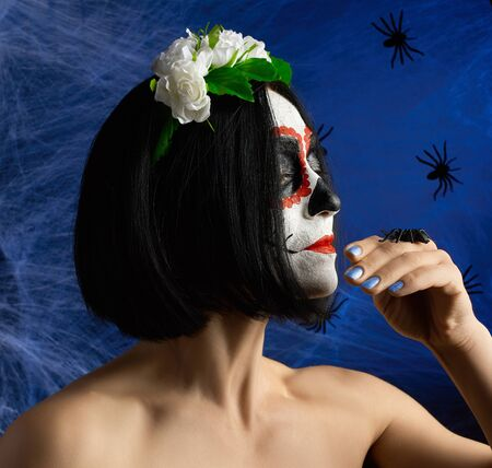 adult beautiful girl with traditional mexican death mask. Calavera Catrina. Sugar skull makeup. girl dressed in a wreath of white roses Banque d'images - 133528776
