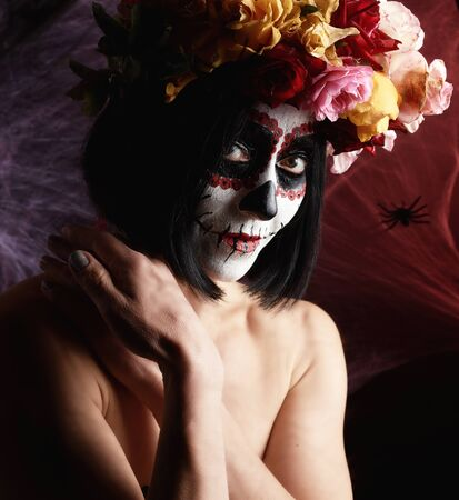 beautiful girl with traditional mexican death mask.  Sugar skull makeup. girl dressed in a wreath of roses on a background of white web Banque d'images - 133528779