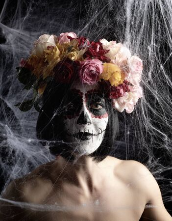Portrait of a young girl with makeup  for the holiday of the Day of the Dead. Sugar skull makeup. spider web background with black spiders Banque d'images - 133530290