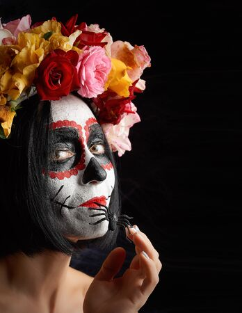 girl with black hair is dressed in a wreath of multi-colored roses and makeup is made on her face Sugar skull to the day of the Dead. Woman looking at the camera Banque d'images - 133530291
