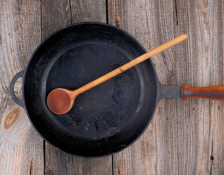 wooden spoon and empty black round frying pan with wooden handle on a gray table, top view