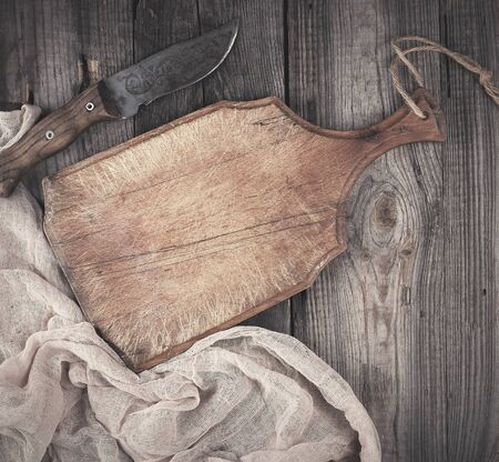 empty old wooden kitchen cutting board and knife on a  table, view from the top Stock Photo