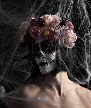 girl with black hair is dressed in a wreath of multi-colored roses and makeup is made on her face Sugar skull to the day of the Dead. Woman looking at the camera through a white web with spiders Banque d'images - 133530296