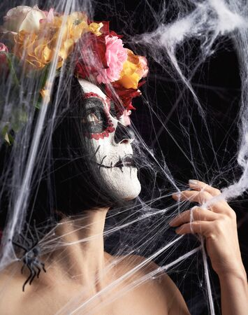girl with black hair is dressed in a wreath of multi-colored roses and makeup is made on her face Sugar skull to the day of the Dead Banque d'images - 133530298