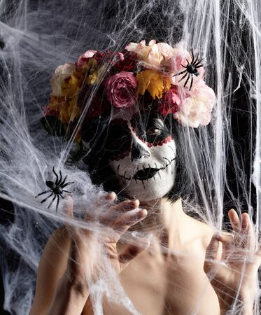 girl with black hair is dressed in a wreath of multi-colored roses and makeup is made on her face Sugar skull to the day of the Dead. Woman looking at the camera through a white web with spiders Banque d'images - 133530299