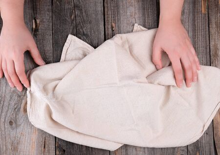 beige textile kitchen towel and two hands on a gray wooden background, top view