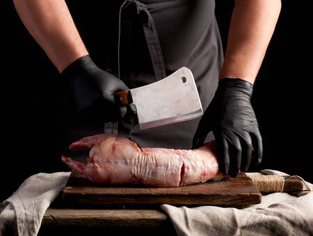 chef in black latex gloves holds a big knife and cuts into pieces raw rabbit meat on a brown wooden cutting board, cooking on a dark background Stock Photo