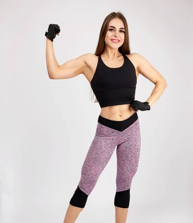 beautiful young woman bodybuilder with long blond hair standing in full length and looking at the camera on a white background, dressed in tights and a black top Reklamní fotografie