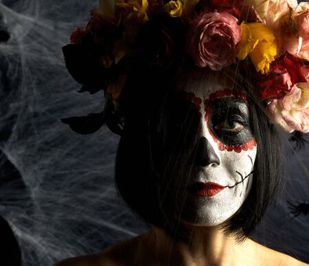 beautiful girl with traditional mexican death mask.Sugar skull makeup. girl dressed in a wreath of roses on a background of white web Banque d'images - 133530322