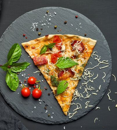 delicious triangular slice of pizza with smoked sausages, mushrooms, tomatoes, cheese and basil leaves on a black graphite board, top view
