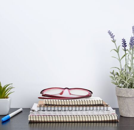 stack of spiral notebooks next to a ceramic pot with a flower on a black table, white wall, Scandinavian-style minimalism