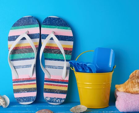 pair of female beach slippers, a yellow baby bucket and scattered seashells on a blue wooden background Фото со стока - 133676961